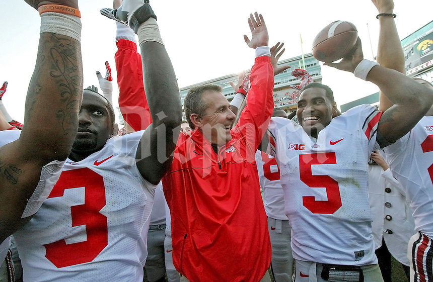 "Ohio State University Head Football Coach Urban Meyer looks to Ohio State Buckeyes quarterback Braxton Miller (5) and smiles while singing ""Carmen Ohio"" at the end of their winning game against Michigan State University at Spartan Stadium in East Lansing, Michigan on September 29, 2012. (Columbus Dispatch photo by Brooke LaValley)"