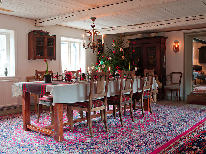 On the colourful Turkish rug in the dining room stands a long dining table in pine made by Bo Stridsby matched with a set of Swedish oak chairs