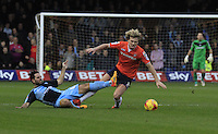 Sam Wood (blue) slides in on Cameron McGeehan (orange)  during the Sky Bet League 2 match between Luton Town and Wycombe Wanderers at Kenilworth Road, Luton, England on 26 December 2015. Photo by Liam Smith.