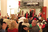 Fred Frost and other members of the Petaluma Area Pilots Association join in the applause for the carolers at the 2017 Holiday Potluck Party, Petaluma Hotel, Petaluma, California