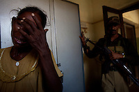 """The mother of a Tamil man, killed the night before by unknown gun men  cries while interrogated by government police officers in a hospital, near the city of Batticaloa, in Eastern Sri Lanka on Thursday, October 12 2006..The Sri Lanka civil was is an ongoing conflict on the island nation of Sri Lanka Since the 1983 """"Black July""""  pogrom there has been on and off civil war, mostly between the government and the Liberation Tigers of Tamil Eelam, or the LTTE, who want to create an independent state of Tamil Eelam in the north east of the island. It is estimated that the war has left 65000 people dead since 1983 and caused great harm to the population and economy of the country. A cease fire was declared in 2001, but hostilities renewed in late 2005. Following escalation of violence         in July 2006, a senior rebel leader declared the ceasefire null and void, although both sides later reaffirmed their commitment to the ceasefire agreement. Hundreds of people, including military personnel, rebels, and Tamil, Sinhalese and muslim civilians have been killed in fighting this year. Thousands of civilians have been displaced, many coming from areas already stroke by the dec 2004 Tsunami.."""