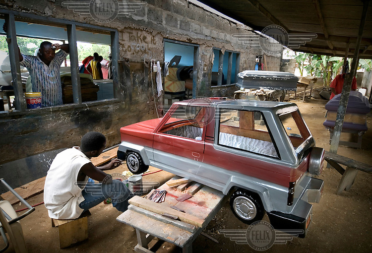 Local carpenters carve out a car shaped coffin. In recent years it has become a custom in parts of Ghana to bury people in specially shaped coffins depicting the deceased person's profession, hobby or even cause of death.