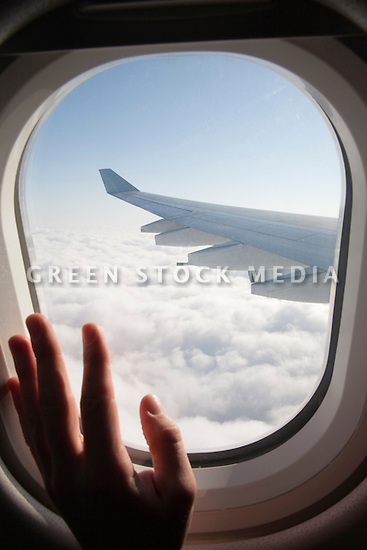 A passenger's hand on an airplane window. The airplane is Airbus A340, operated by Cathay Pacific airline.