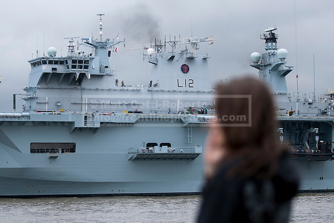 04/05/2012. LONDON, UK. A member of the public watches HMS Ocean, the Royal Navy's helicopter carrier, after she made her way up the Thames to moor in Greenwich, London, today (04/05/12). HMS Ocean has been deployed as part of an exercise involving the RAF, British Army and Royal Navy taking place across London as part of security preparations for the 2012 London Olympic Games. Photo credit: Matt Cetti-Roberts