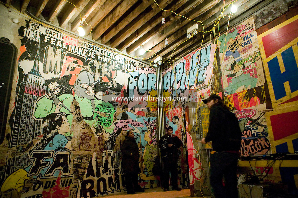 15 December 2006 - New York City, NY - People walk through a three-day street art exhibition entitled Wooster on Spring held in the 19th-century brick building at 11 Spring Street in the NoLIta neighborhood of New York City, USA, 15 December 2006. The building's new owners, Caroline Cummings and Bill Elias, called on the Wooster Collective to curate the show as a last hurrah for a site that long served as a canvas for street art.&amp;#xA;<br />