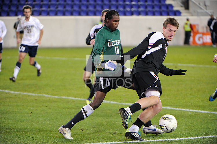 Connecticut Huskies goalkeeper Andre Blake (18) defends Colin Rolfe (9) of the Louisville Cardinals. Connecticut defeated Louisville 1-0 during the first semifinal match of the Big East Men's Soccer Championships at Red Bull Arena in Harrison, NJ, on November 11, 2011.