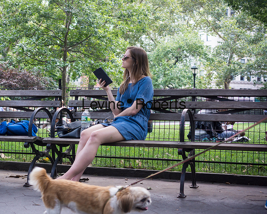 A visitor to Madison Square Park in New York reads on her Amazon Kindle ereader on Sunday, July 20, 2014.  (© Richard B. Levine)
