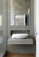 A contemporary grey tiled bathroom with a mirror hanging above a bowl washbasin set on a wall-mounted shelf. Glass mosaics in a floral pattern on the opposite wall are reflected in the mirror.