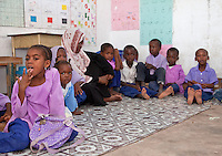 Jambiani, Zanzibar, Tanzania.  Primary school classroom and children.  These Muslim  children are learning the Arabic alphabet so they can read the Koran, and the Latin alphabet so they can read English and Swahili.  English is the language used in higher education and the courts in Tanzania.