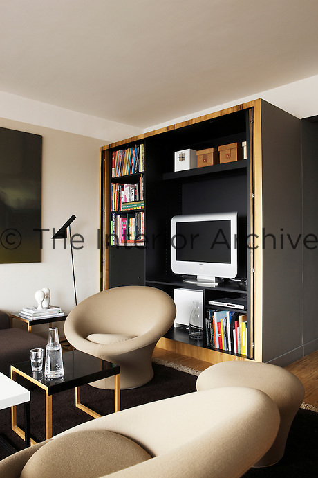 In this Paris apartment the television and bookcase can be open to view or concealed behind painted cupboard doors