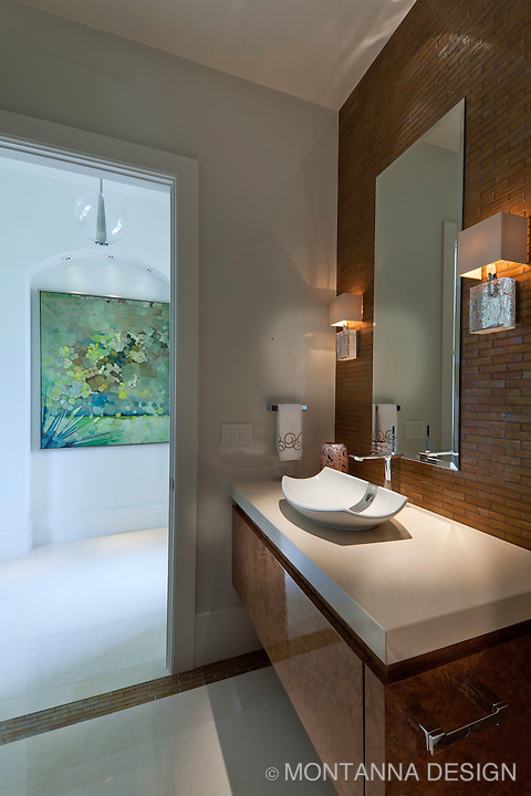 The powder bath has unique brick lay patterned glass tile backsplash with vessel lavatory.