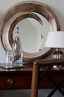 A circular mirror is placed above a wood console table in a guest bedroom at the Hotel Tresanton