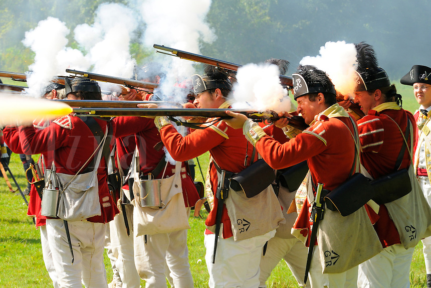 British redcoats of His Majesty's 20th Regiment of Foot fire muskets during a Revolutionary War re-enactment at Fort Ticonderoga, New York, USA.