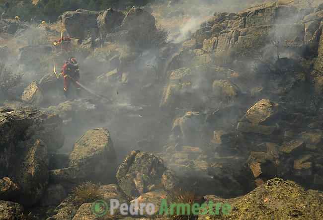 Members of the Spanish Army Emergency Unit (UME) try to extinguish a fire burning in the Cerro del Castillo hill near the town of Collado Mediano, northeast of Madrid, which forced the evacuation of some 2,000 people, the mayor of the town, Maria Rubio, told news radio Cadena Ser on July 21, 2009. Four firefighters were killed and two were seriosuly injured Tuesday as they battled another wildfire in a natural park in northeastern Spain, a spokeswoman for the local government said. on July 21, 2009. (C) Pedro ARMESTRE
