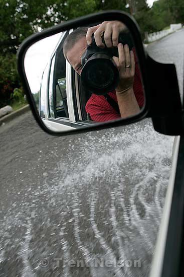 trent nelson in mirror driving through flood water. Flooding along 700 South in Tooele Tuesday.<br />