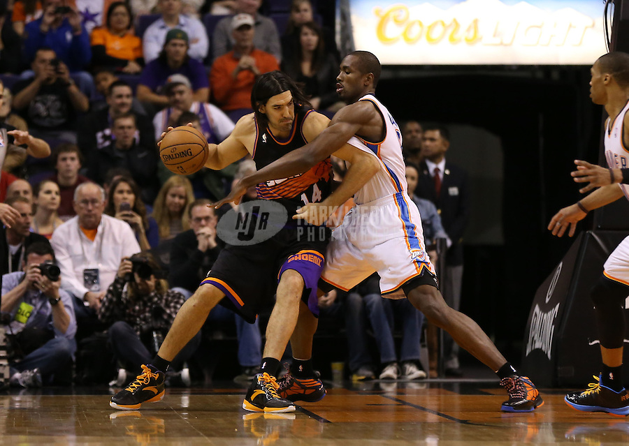 Feb. 10, 2013; Phoenix, AZ, USA: Phoenix Suns power forward Luis Scola (left) drives to the basket against Oklahoma City Thunder forward Serge Ibaka at the US Airways Center. Mandatory Credit: Mark J. Rebilas-