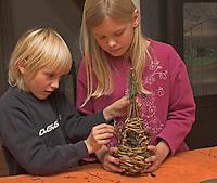 Kinder flechten Nistkugel für Vögel, Vogel, Nisthilfe, Nest, Kugelnest. Nest wird mit Moos und Schilfblüten ausgekleidet