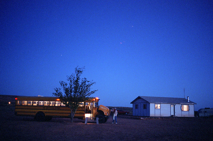At 5:15 A.M., William Mustache finishes the inspection of his bus at his home 45 minutes south of Blanding, Utah. Mustache drives a school bus for the San Juan School District in southeastern Utah, which includes a strip of the vast Navajo reservation. Trips on his bus are some of the longest in the coutry, at an hour and 45 minutes each way for some of his riders. (Photo/Kevin Moloney for the New York Times)