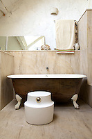 "Local stone from Souppes-sur-Long was used in constructing the bathroom walls and floor; the ceramic and silver ""Lunge"" stool is a design by Eric Schmitt as is the plaster wall light"