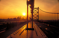 The Ben Franklin Bridge which spans the Delaware River frames the Philadelphia city skyline at sunset. Philadelphia Pennsylvania United States skyline.