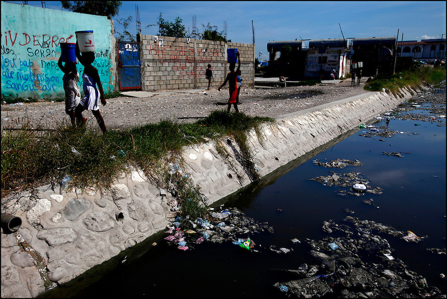 Nov 10, 2010 - Port-au-Prince, Haiti.Residents of the Cite Soleil area of Port-au-Prince, Haiti carry water gathered from a well just yards away from a river of human waste and garbage on Wednesday, November 10, 2010 as fears of a Cholera outbreak spread through the area just two days after cases of the infection were confirmed in the area, the poorest slum in Haiti's capital. Officials from the Pan American Health Organization warn that Haiti's cholera epidemic, spread primarily through consuming infected water and food, is likely to grow much larger in the wake of Hurricane Tomas.  (Credit Image: Brian Blanco)