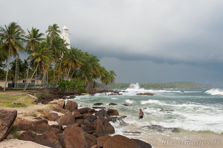 Boy plays in waves with storm clouds overhead at Dondra Head Lighthouse on the southern tip of Sri Lanka.