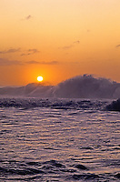 Waves and surf off North Shore Oahu with the sunset in the background