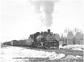 D&amp;RGW #486 with freight train passing oil storage tanks at Gunnison.<br /> D&amp;RGW  Gunnison, CO  Taken by Richardson, Robert W. - 3/29/1952