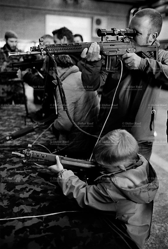 "Switzerland. Canton Bern. Thun. A father and his son hold machines guns. Both play with with an automatic or semi-automatic assault rifle SG 550 at a swiss army stall during the military event ""Thun meets Army & Air Force"". The SG 550 is an assault rifle manufactured by Swiss Arms AG (formerly Schweizerische Industrie Gesellschaft) of Neuhausen, Switzerland. ""SG"" is an abbreviation for Sturmgewehr, or ""assault rifle"". The rifle is based on the earlier 5.56mm SG 540 and is also known as the Fass 90 or Stgw 90. An assault rifle is a selective-fire rifle that uses an intermediate cartridge and a detachable magazine. 21.10.2016 © 2016 Didier Ruef"