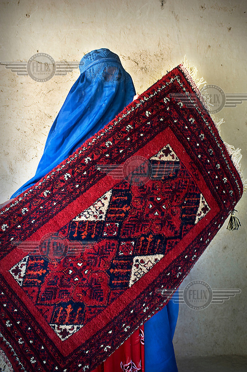 A carpet weaver, wearing a blue burqa, holds up a rug woven with traditional motifs.