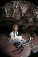 A portrait of a young woman reading in a lava cave at Hawai'i Volcanoes National Park, Big Island of Hawai'i.