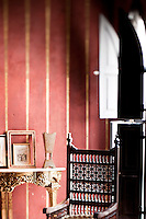 Detail of the back of an ornately carved wooden chair and a gilded console table in the exotic red and gold bedroom