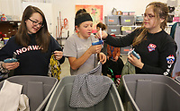 NWA Democrat-Gazette/DAVID GOTTSCHALK Caroline Pauls (from left), 14, a volunteer with Arkanserve a volunteer group from New Heights Church, Brooke Sheffler, 17, volunteer with the church, and Abigail Wilmoth, a volunteer with Sigma Alpha Sorority at the University of Arkansas, tag donated items Tuesday, March 19, 2019, at the new location of Beautiful Lives Thrift Boutique at 245 East Township Street in Fayetteville. The non profit, that supports five organizations for women and children in crisis. The boutique is also the new location of The Global Shoppe that offers handmade products made by women to enhance the lives of women.