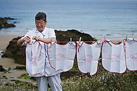 Europe/France/Bretagne/29/Finistère/Cléden Cap Sizun : Huguette le Gall du restaurant  l'Etrave  réputée  pour sa marmite de homard étend les bavoirs du restaurant représentant des homards