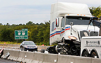 NWA Democrat-Gazette/DAVID GOTTSCHALK A semi truck is prepared for transport as members of the Fayetteville Fire Department and other emergency personnel clear the northbound lane of Interstate 49 south of the Porter Road exit Friday, September 11, 2015 following a semi truck accident in Fayetteville. The vehicle hit the guard rail on the interstate shutting down one lane and spilling 125-150 gallons of fuel and oil.