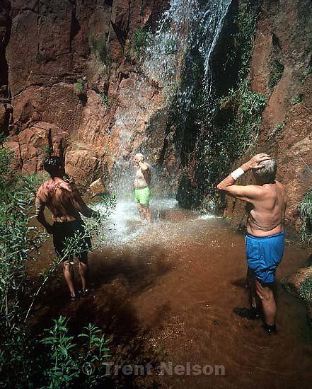 Men in waterfall. Grand Canyon flood trip.<br />