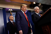 United States President Donald J. Trump, center, listens to US Vice President Mike Pence, right, speak during a press briefing on the Coronavirus COVID-19 pandemic with members of the Coronavirus Task Force at the White House in Washington on March 19, 2020. At left is Stephen Hahn, Commissioner, United States Food and Drug Administration (FDA).<br /> Credit: Yuri Gripas / Pool via CNP/AdMedia