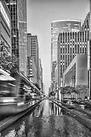 This is a black and white image of the Houston rail system in early evening as on of the trains zooms by in a blur in front of a water feature between the tracks in downtown Houston. You can see the skyline with all the high rise buildings along the path through the city on its route outside of the area.