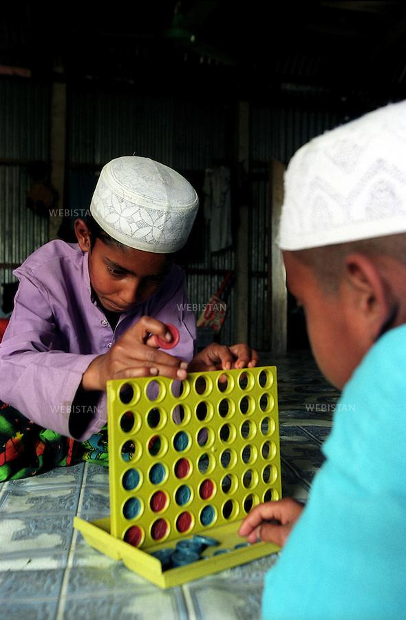 2005..Bangladesh. In a madrassa, Muslim pupils play a game to relax. .Bangladesh. Dans une madrassa, des élèves musulmans jouent à un jeu pour se détendre.