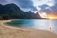 A girl plays near the sandbar at sunset at Tunnels Beach, Ha'ena, Kaua'i.