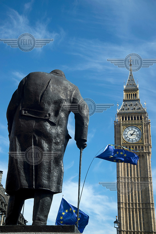 An EU flag with the statue of Winston Churchill and the Clock Tower of the Houses of Parliament during a 'Unite for Europe March on Parliament'.