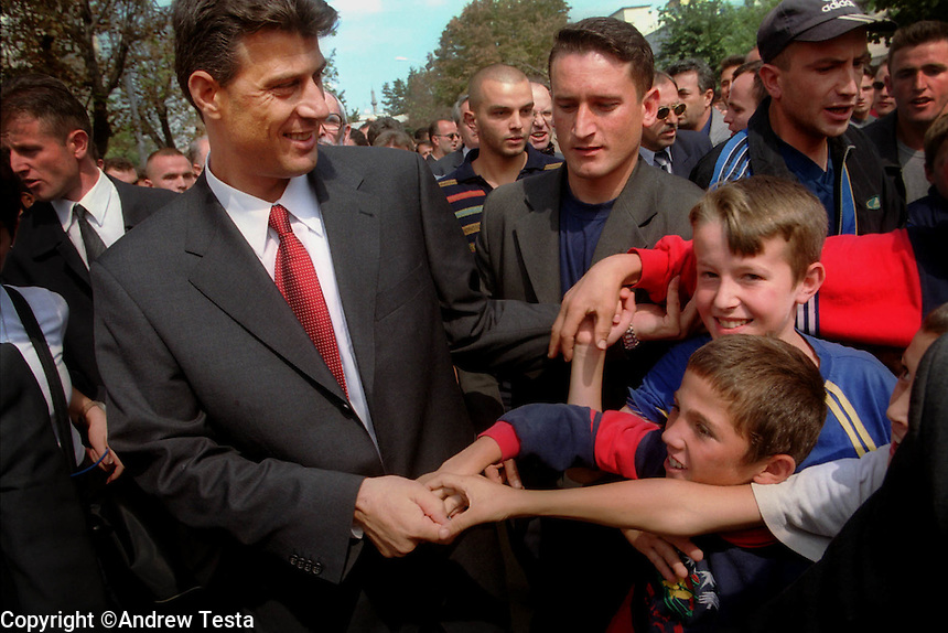 KOSOVO. Pristina. 09/09/2000..Hasim Thaci, ex leader of the KLA and now the leader of its political wing the PDK, greets children during the March Against Violence..©Andrew Testa