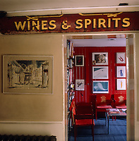 A salvaged vintner's sign hangs above the entrance to the 'red office'