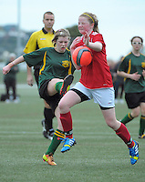 Action from the Wellington girls college football bronze playoff final between Sacred Heart College (red) and Wellington High School (green and gold) at Wakefield Artificial Turf,  Wellington, New Zealand on Wednesday, 21 August 2013. Photo: Dave Lintott / lintottphoto.co.nz