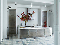 The kitchen features custom-made cabinetry with aged stainless steel doors and fitted with vintage hardware, 1950s sconces by Gunnar Asplund, and 1970s light fixtures; the sink fittings are by Dornbracht, and the countertops are white glass.