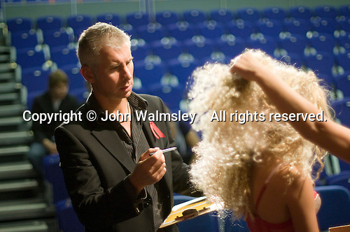 Competitors describe their entries to a judge in the annual X-Foto competition in the Hair & Beauty Department at Kingston College, London.