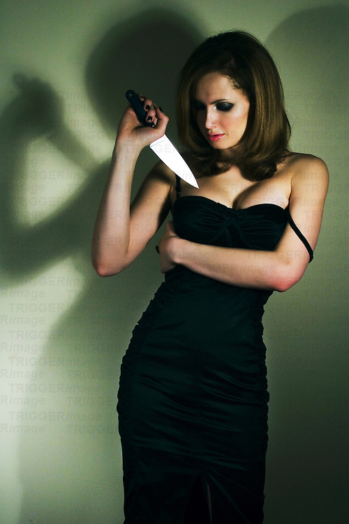 A young woman wearing a black dress holding a knife to her chest