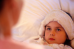 Young girl ( 7 years old) in bed with flu/cold with mother and washcloth on forehead.