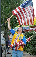 NWA Democrat-Gazette/DAVID GOTTSCHALK Chris Smiley, a Fayetteville Lions Club member, posts Monday, October 8, 2018, a United States Flag on a street lamp post on the downtown square in Fayetteville. The installation of the flags on holidays is a service project for the club and are posted through out the city including Dickson Street, the downtown square and parts of College Avenue.