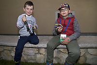 """Children of Cocullo.The feast of snakes. Process dedicated to the Saint Dominic, in the streets of Cocullo, in the Abruzzo region, Italy on May 1, 2019.<br /> <br /> <br /> The St. Domenico's procession in Cocullo, central Italy. Every year on the first  of May, snakes are placed onto the statue of St. Domenico and then the statue is carried in a procession through the town. St. Domenico is believed to be the patron saint for people who have been bitten by snakes:<br /> <br /> Italy, Cocullo, in the Province of L'A...quila, is at 870 meters a.s.l., along the railway line connecting Sulmona to Rome. The village rises alongside Mount Luparo (1327 meters) """"The valley opening in front of the village is surrounded by bare rocks, while on the other side, to the south, snow-capped mountain crests follow one after the other...""""<br /> San Domenico Abate lived in the 10th and 11th centuries AD. Born in Foligno, in the Umbria region, he started his pilgrimages, preaching and ascetic practices in Central Italy, making miracles recorded by the word-of-mouth tradition. He died on 22 January 1031 and was buried in Sora.<br /> <br /> Cocullo snake charmers are over with their snake hunting. They proceeded through the During the procession on the first in May, before the snakes are placed all over the statue of St. Dominick, they will be fed with milk kept in containers with crusca. It is the snake that, most of all other elements, expresses an ancestral myth: the unknown aspect and unpredictability of the natural environment with man's innate need to achieve the dominance on his own habitat. <br /> <br /> Snakes and wolves were the emblems of Italic peoples like the Marsians and Irpinians. Some areas in Abruzzo, especially in the Sagittario valley, were under the menace of wolves and snakes, which for the local populations represented the uncertainty and anxiety of their existence that, together with the precariousness and hardships of life, were almost unbearable. Therefore the co"""